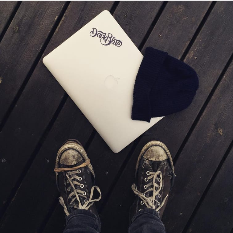 Darkblue branded laptop with Iggy's shoes